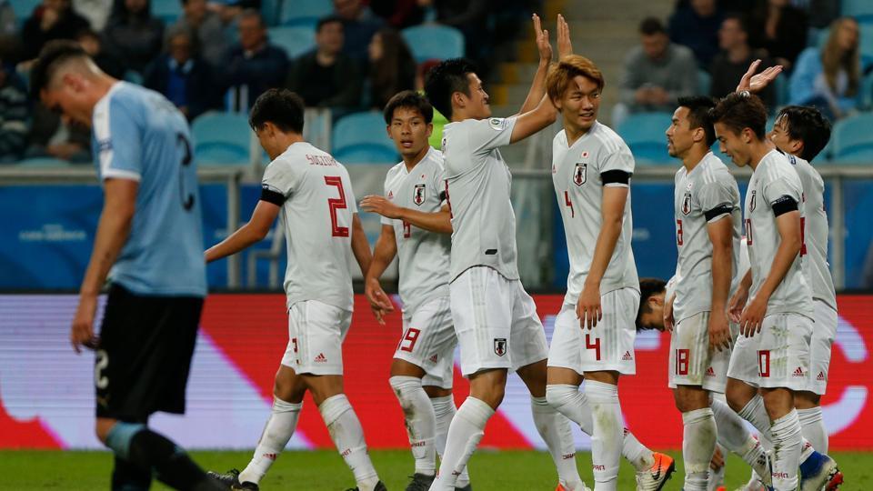 Japan's Koji Miyoshi(R) celebrates with teammates after scoring his second goal.