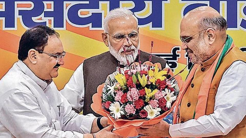 In the presence of PM Narendra Modi, Home minister Amit Shah gives a bouquet to JP Nadda (Left) after he was appointed BJP working president on June 17.