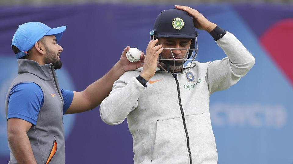 India's Rishabh Pant, left, gestures as MS Dhoni wears his helmet to bat in the nets during a training session ahead of their Cricket World Cup match against Afghanistan