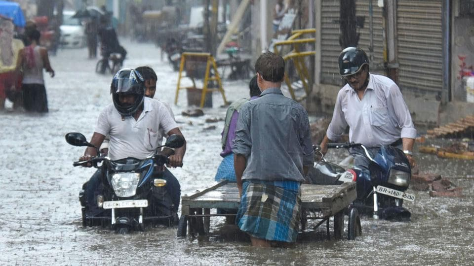 Commuters wade through a waterlogged street after pre-monsoon rain, in Patna. The weather conditions that were forecasted by the Indian Meteorological (IMD), Patna centre predicted that the city is likely to see thunderstorm with lightning today and tomorrow and receive heavy rain for two days from June 24. (PTI)