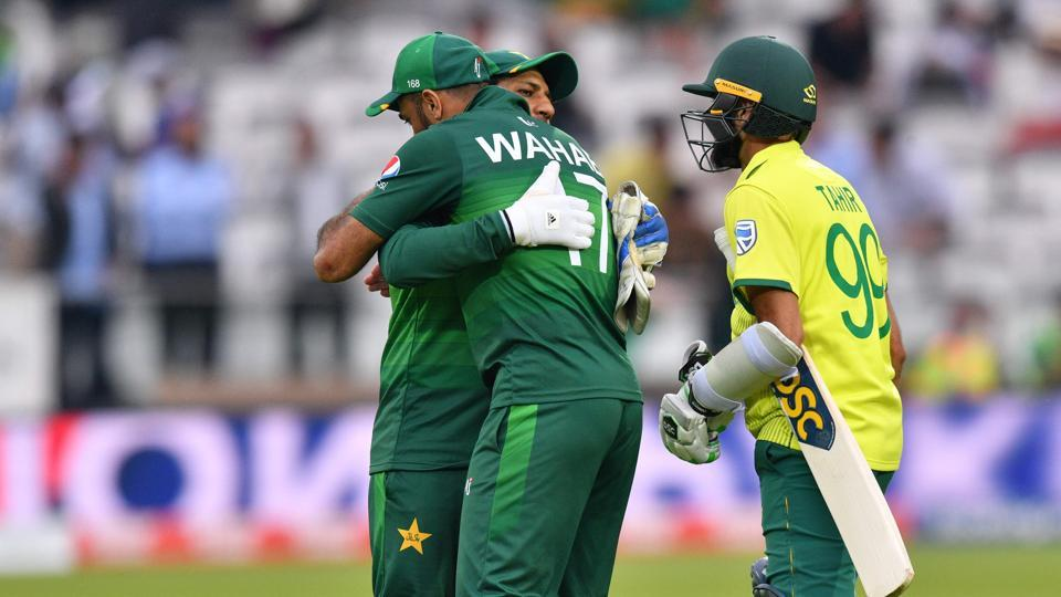 Pakistan's captain Sarfaraz Ahmed (C) embraces teammate Pakistan's Wahab Riaz (L) while South Africa's Imran Tahir (R) looks on as he celebrates with his players after victory in the 2019 Cricket World Cup group stage match between Pakistan and South Africa at Lord's Cricket Ground in London on June 23, 2019