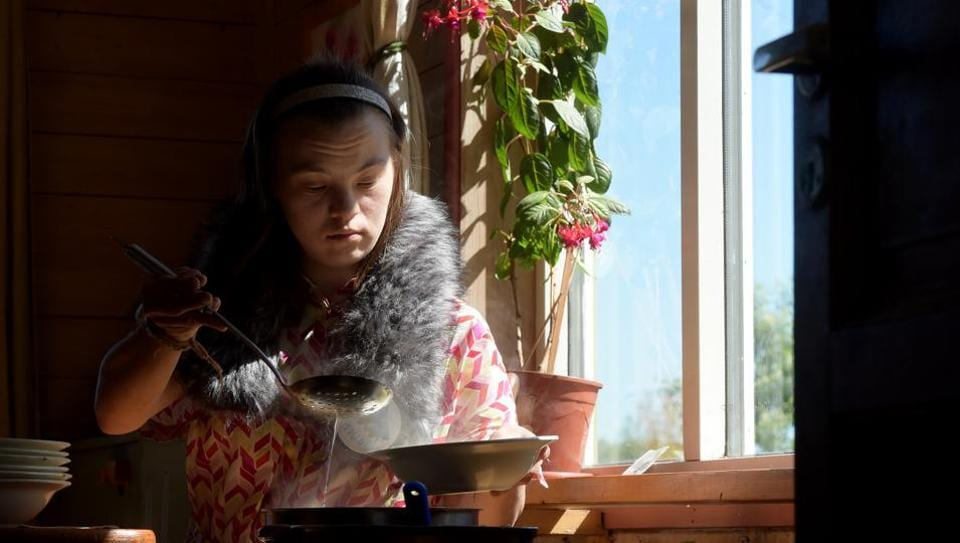 """Natasha, 21, who has Down syndrome, serves lunch to residents of the Svetlana farm outside the settlement of Aleksino, Russia. On a warm sunny day, 37-year-old Vika walked through a farmyard carrying a compost bin, saying to AFP with pride: """"This is my job."""" She's one of 18 Russians with learning disabilities to live and work on the Svetlana farm which has a dairy and bakery where residents do daily chores and therapy. (Olga Maltseva / AFP)"""