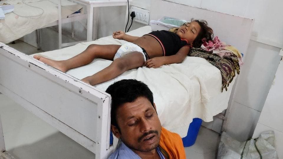 A man sleeps next to his daughter who is suffering from acute encephalitis syndrome at a hospital in Muzaffarpur, Bihar, June 20, 2019.