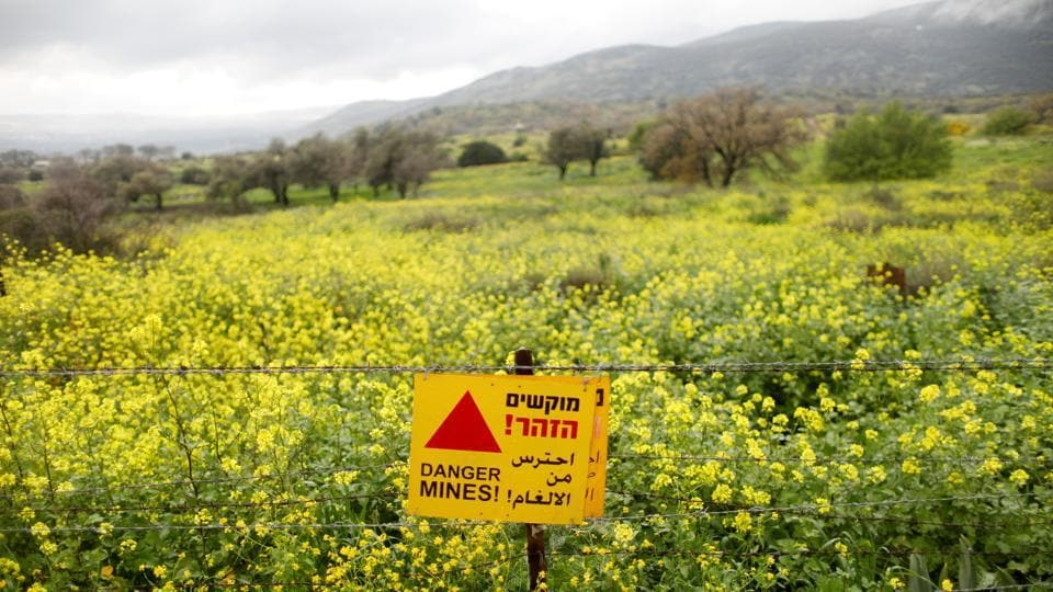 A sign warning of landmines is seen on a fence in the Golan Heights. Many tourists drive past the site on their way to popular holiday spots. Since the end of British Mandate rule and the creation of the modern state of Israel in 1948, invasions, wars, armistices, treaties, uprisings, barriers, checkpoints and civil wars have shifted the boundaries of who can travel - and live - where. (Ronen Zvulun / REUTERS)