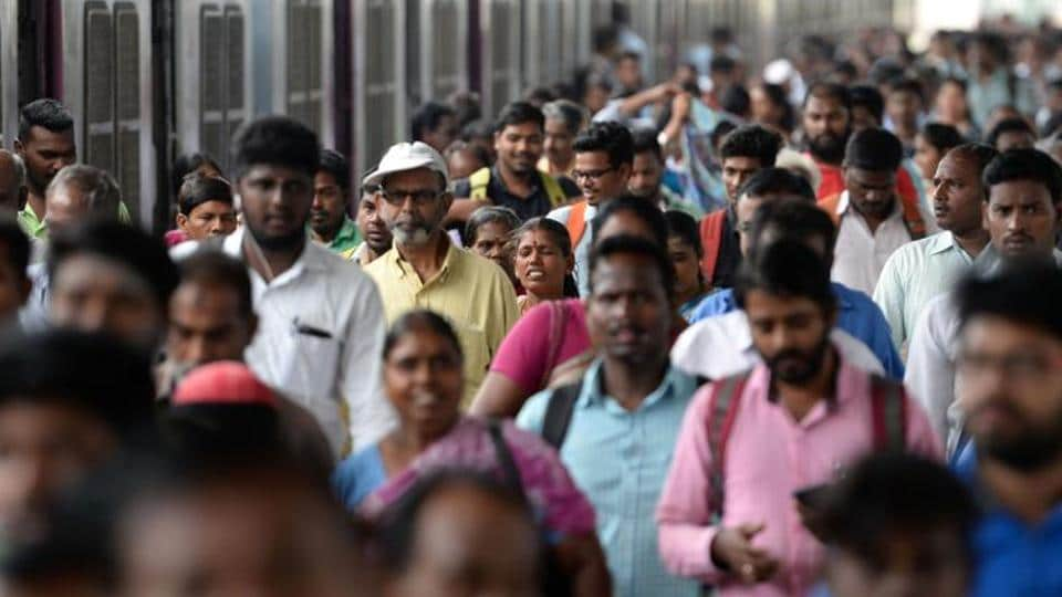 Indian commuters make their way through a central railway station at rush hour on World Population Day in Chennai on July 11, 2018. / AFP PHOTO / ARUN SANKAR