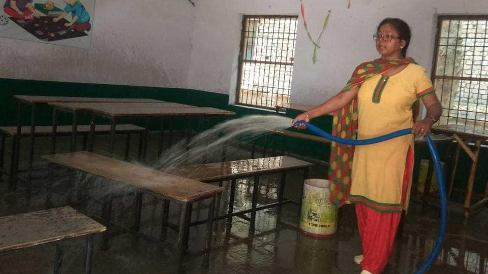 A teacher in primary school (boys) in North Vijay Nagar Colony, Agra, cleaning a classroom on Wednesday, June 26, 2019.