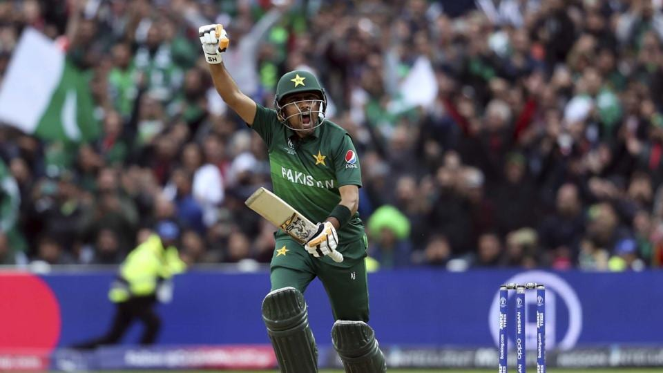 Pakistan's batsman Babar Azam raises his fist to celebrate scoring a century.
