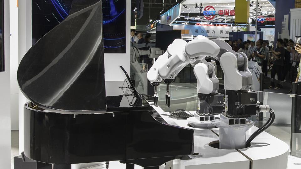 Attendees watch a demonstration performed by robotic arms at the MWC Shanghai exhibition in Shanghai, China.