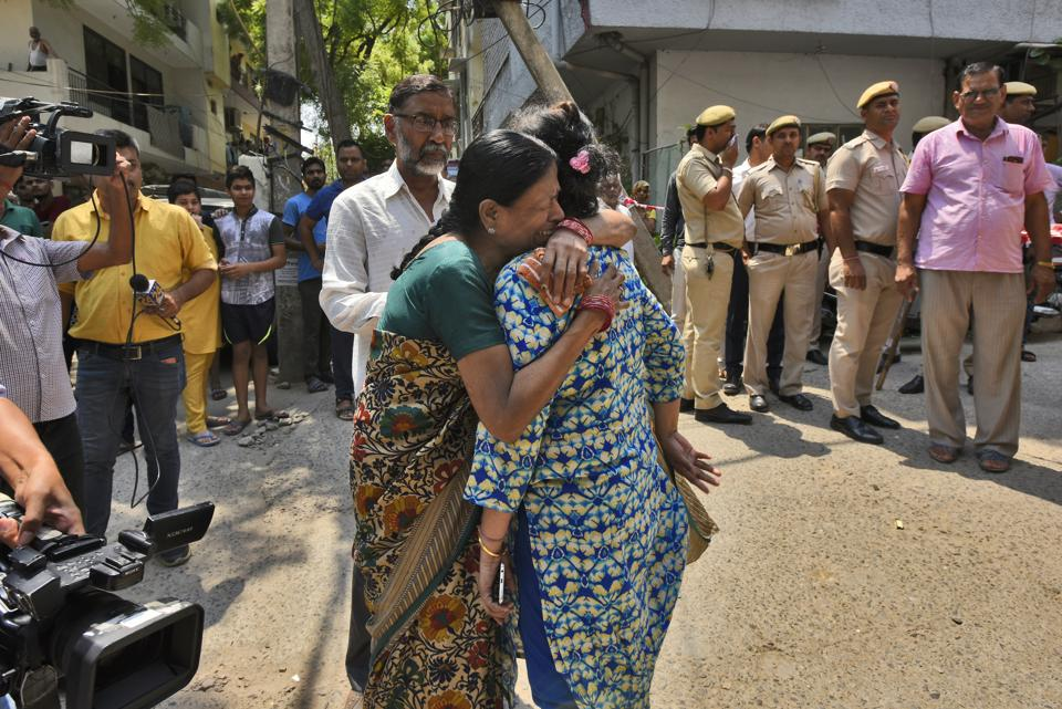 The daughter (R) of an elderly couple who were found murdered along with their domestic help at their house, is comforted by a relative, at Vasant Apartments, in Vasant Vihar.