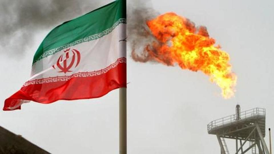 A gas flare on an oil production platform in the Soroush oil fields is seen alongside an Iranian flag in the Persian Gulf, Iran. (REUTERS/Raheb Homavandi/Files)