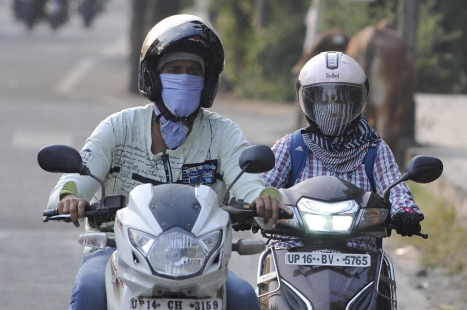 People cover their faces to protect themselves from the scorching heat in Noida.
