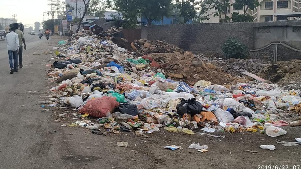 People walk besides piles of garbage dumped on Bakore chowk in Wagholi.