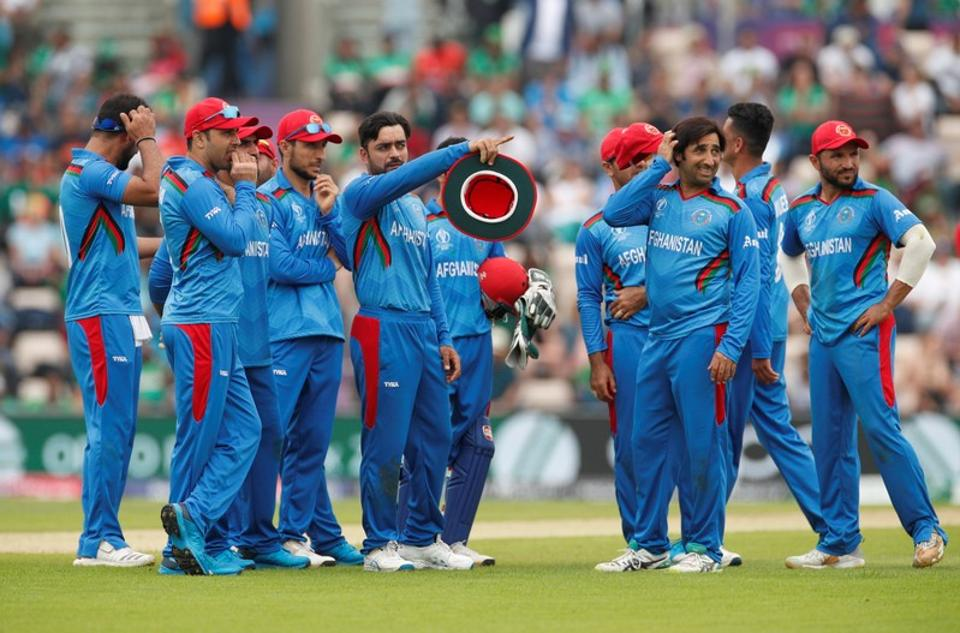 Afghanistan's Rashid Khan and team mates watch a review on the big screen
