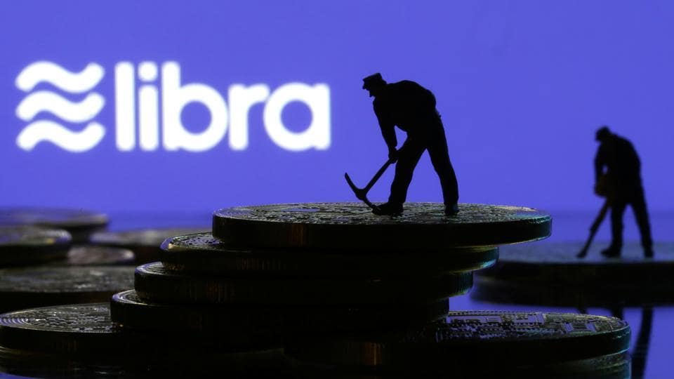 Small toy figures are seen on representations of virtual currency in front of the Libra logo in this illustration picture, June 21, 2019.