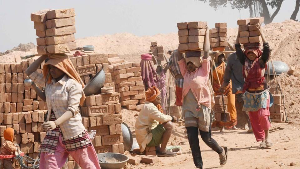 Women carry bricks while working in a brick kiln