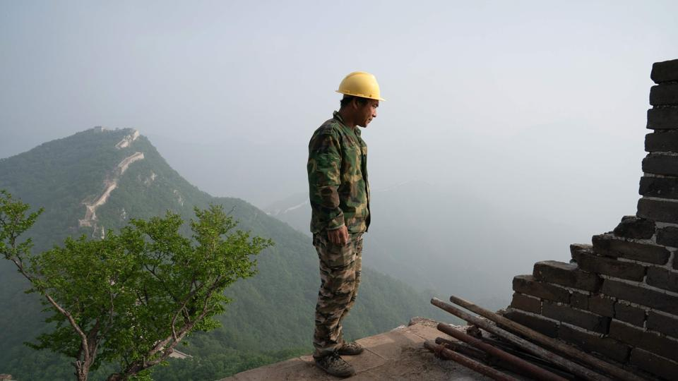 A worker inspecting a restored part of the Great Wall.
