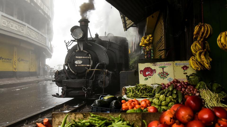 A Darjeeling Himalayan Railway steam train passes by a market in Ghum, West Bengal. The Ghum Station is the highest point reached by the railway (7,407ft), and from here there is a descent for four miles down a spur to Darjeeling Station (6,812ft). The Darjeeling Himalayan Railway (DHR) was the first, and is still the most outstanding, example of a hill passenger railway. (Ranita Roy / REUTERS)