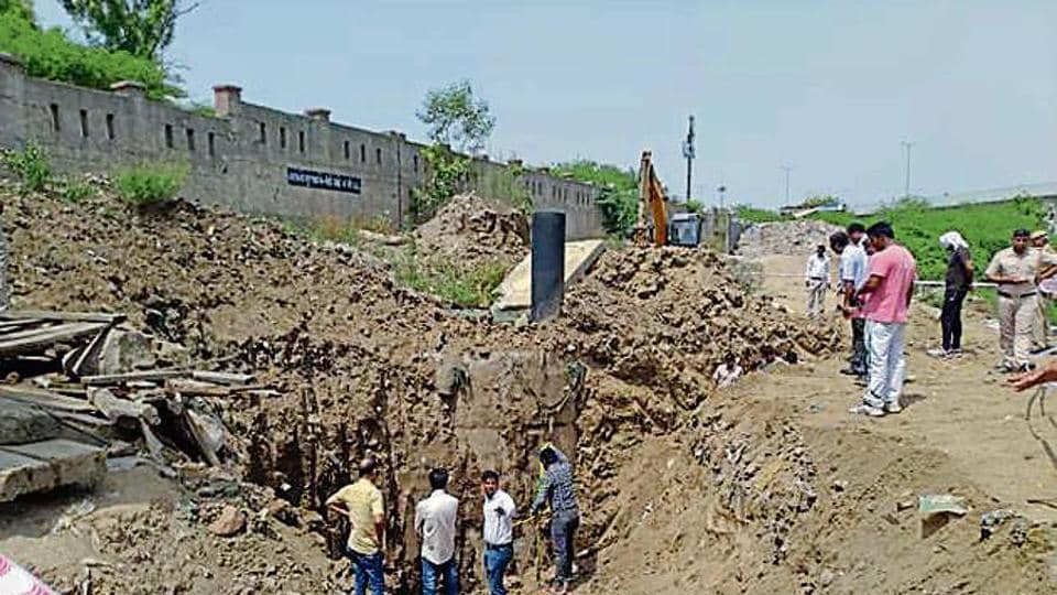 People gather during the search operation to locate the bodies of the two welders who are feared dead in yesterday's Delhi Jal Board drain accident, at Khyala, in New Delhi, India.