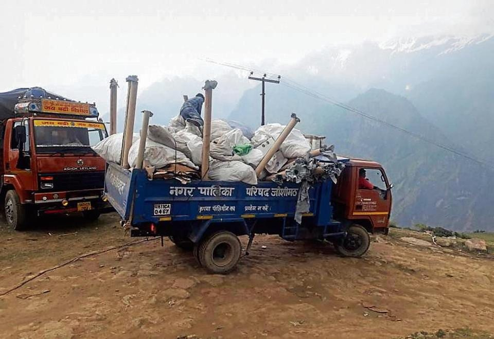 Workers of Joshimath civic body clean up the waste generated after the luxury wedding in Auli.