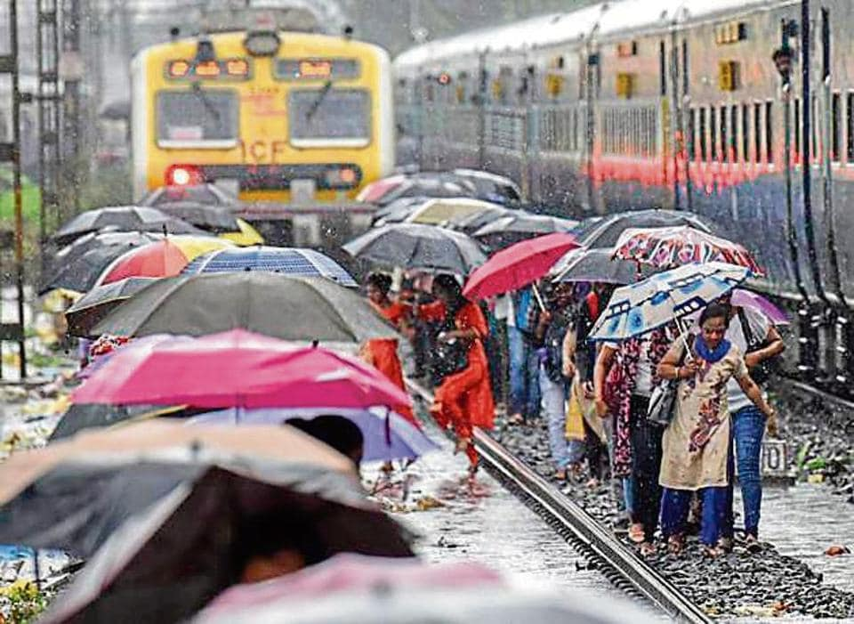 People walk on the railway tracks as heavy monsoon rains hit the local train services near Sion in Mumbai, India, on Monday, July 1, 2019.