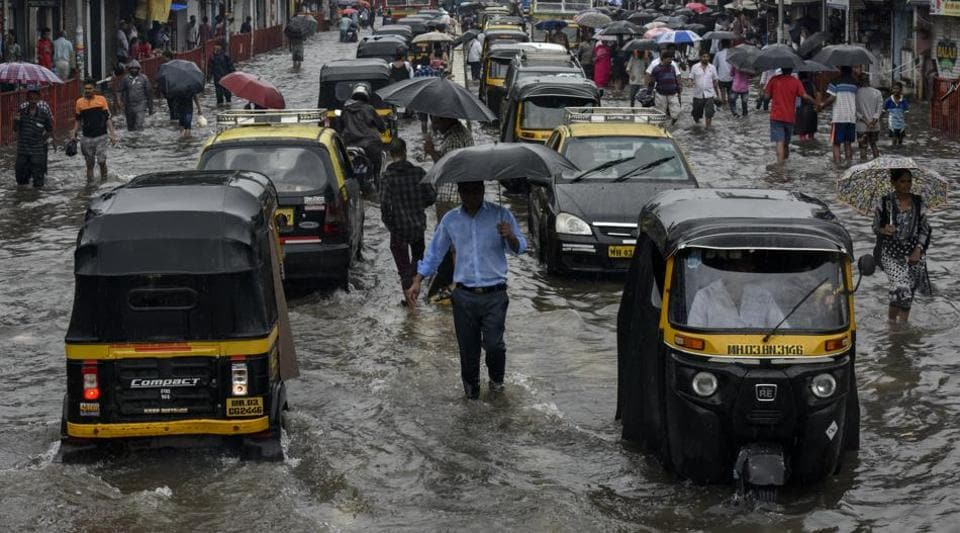 People walk along a flooded street after heavy rain showers outside Kurla station in Mumbai, India, on Tuesday, July 2, 2019.
