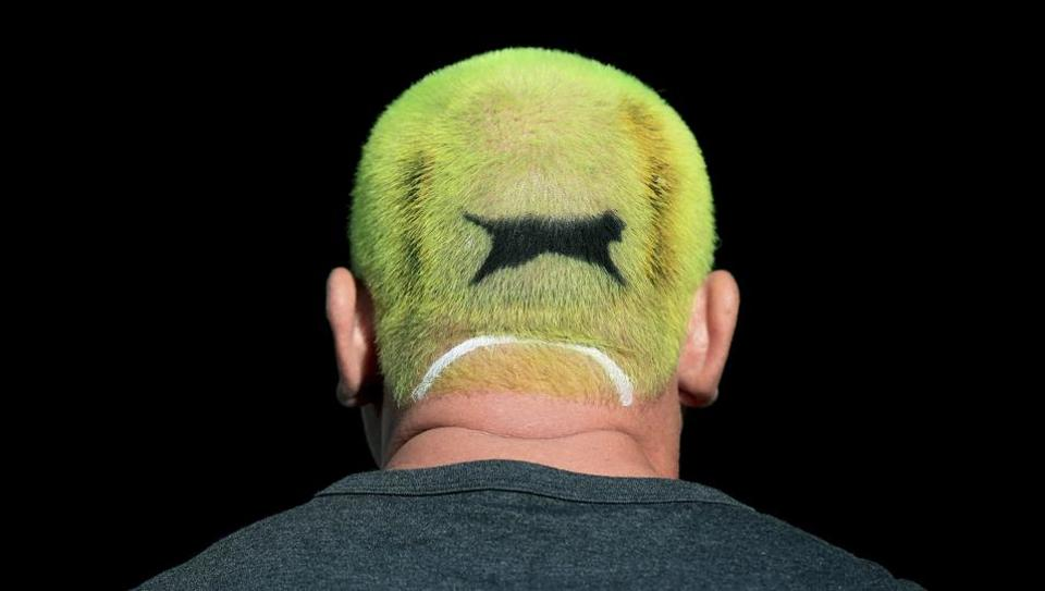 An enthusiastic tennis fan has his hair dyed the colour of a Slazenger ball on day one of the Wimbledon Tennis Championships in London, England on July 1, 2019. Tennis fans from all over the globe have descended on Wimbledon for the world-famous Grand Slam.