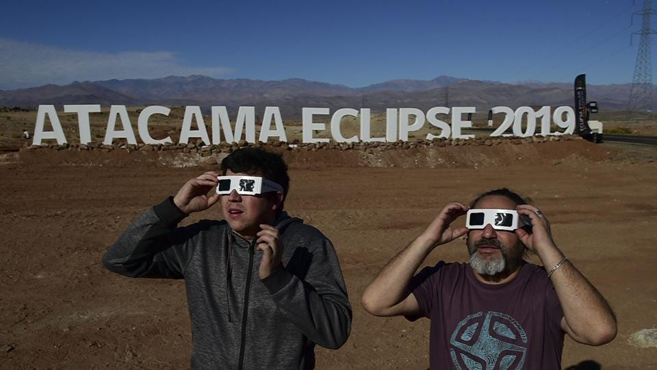 Tourists look at the sun before a solar eclipse in an entrance of an astronomical camp to observe the July 2 total solar eclipse, in the commune of Vallenar in the Atacama desert, Chile, on July 1, 2019.