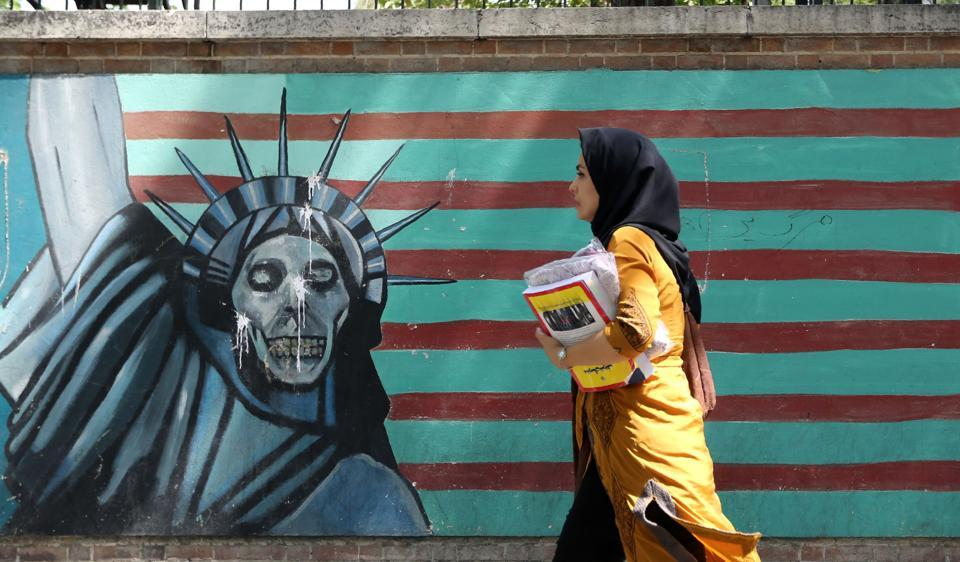 A woman walks past a mural painting along the wall of the former US embassy, Tehran, June 22, 2019