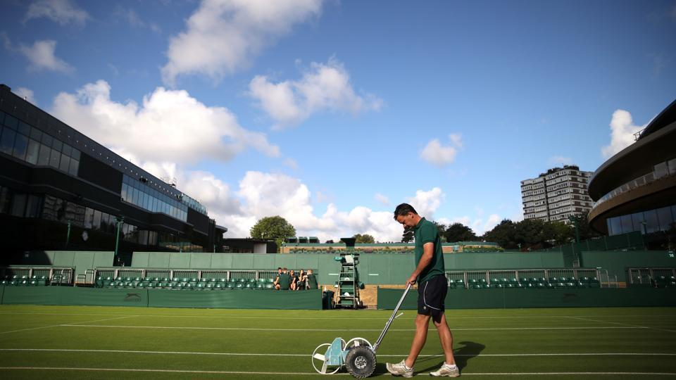 Groundstaff prepare the court before play. Britain's summer burst of heat from across the continent ended being short-lived following a 34C Saturday in London. Cool air from Greenland is said to have plummeted temperatures to highs of 22C and cloudy skies just in time for the first serve. (Carl Recine / REUTERS)
