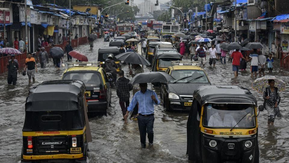 People walk along a flooded street after heavy rain showers outside the Kurla station, Mumbai, July 2, 2019