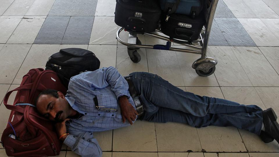 A stranded passenger sleeps next to his luggage as he waits for the delayed flight after an airplane overshot the runway while landing due to heavy rains at the Chhatrapati Shivaji International airport in Mumbai, India July 2, 2019. REUTERS/Prashant Waydande