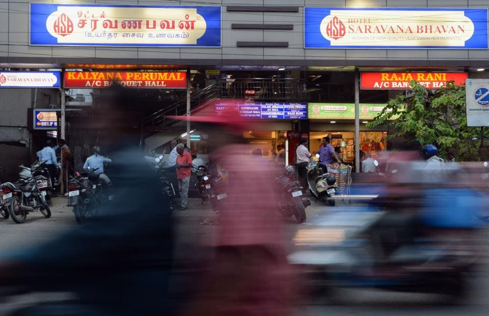 This photo taken on June 28, 2019 shows people outside a restaurant of the popular Saravana Bhavan food chain in Chennai. - Rajagopal's story has it all: rags to riches, the visionary creator of a trailblazing Indian restaurant chain -- and having a love rival murdered after some fateful cosmic advice.