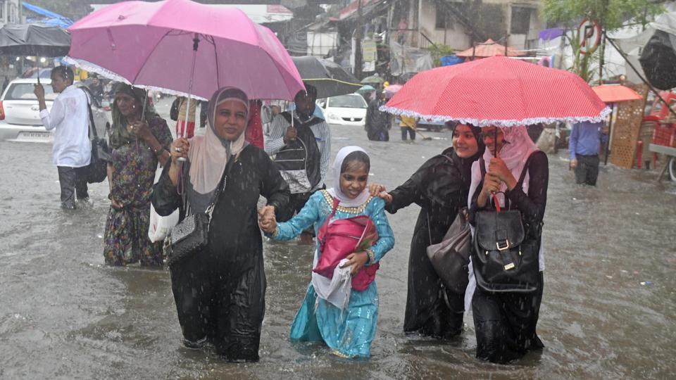 People wade through water-logged road near Andheri Subway(W), in Mumbai.