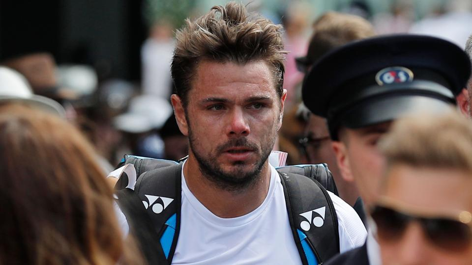 Switzerland's Stan Wawrinka (C) leaves court after losing his men's singles second round match.