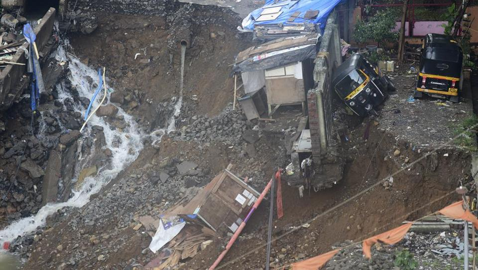 A road caved in at Sangharsh Nagar, Chandivli, Mumbai, on the night of July 1, 2019. forcing evacuation of 100 families from two residential buildings.