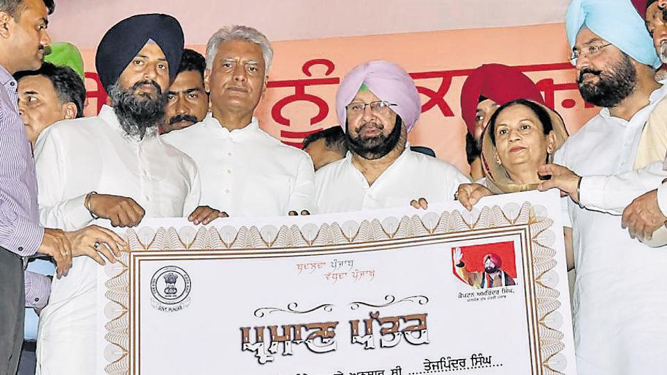 Chief minister Captain Amarinder Singh along with other Congress leaders during the distribution of loan waiver cheques to farmers in Gurdaspur in April , 2018.