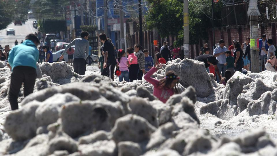 People are seen in a street of Guadalajara, Mexico, after a hail storm fell in the area.