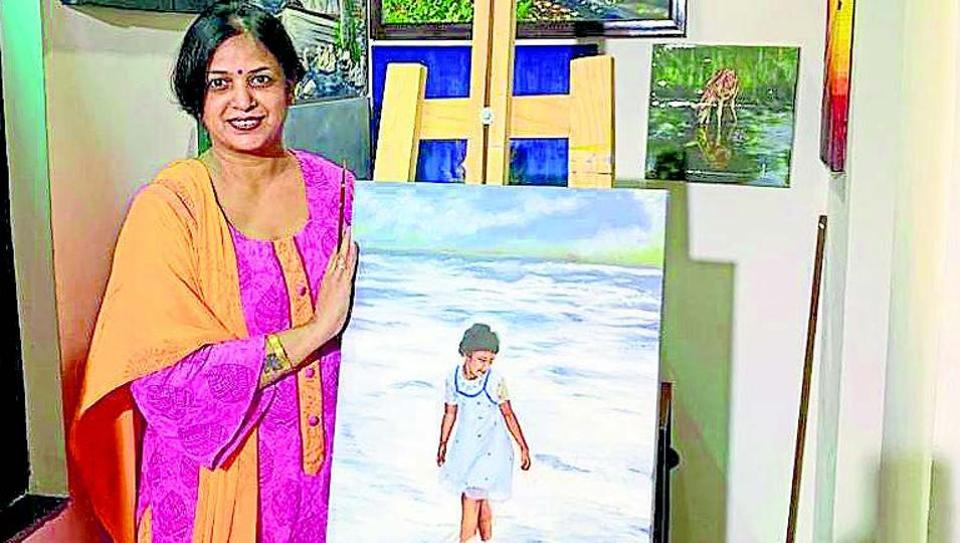 Sudha Sarawagi, 44, with her paintings at her residence in Sector 48.