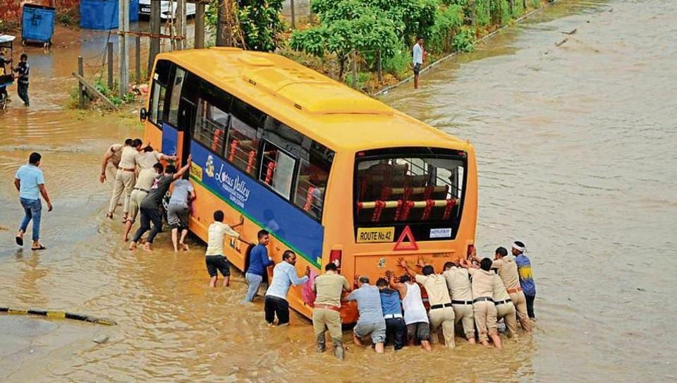 Police personnel push an empty school bus, one of the three vehicles that stalled on a waterlogged road at Subhash Chowk, on Thursday. (Right) Bikers wade their way past cars and buses on a flooded Gurugram-Sohna Road.