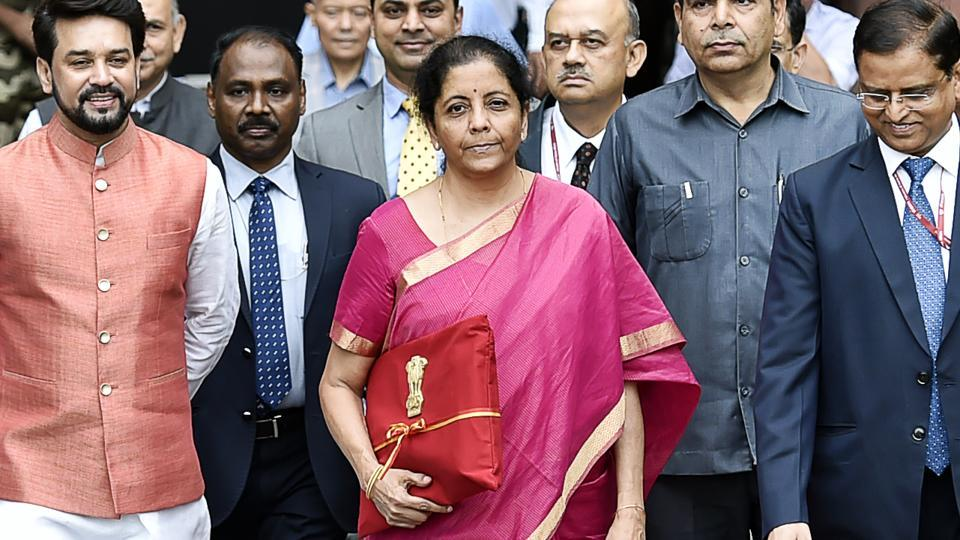 Minister of Finance Nirmala Sitharaman (C) seen holding the Budget folder--Bahi Katha wrapped in red cloth with the National Emblem.