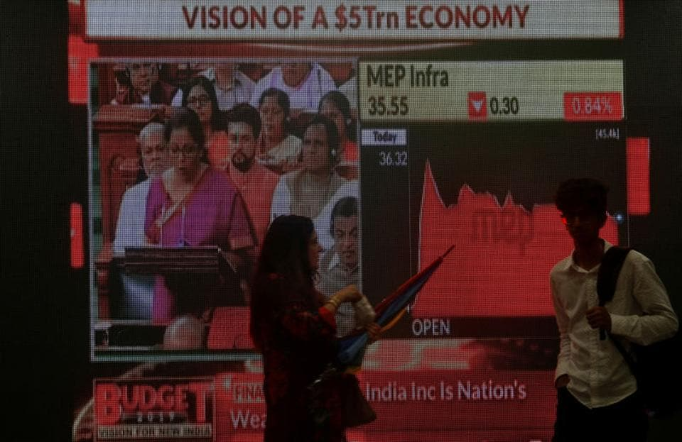 People walk as a telecast of India's Finance Minister Nirmala Sitharaman presenting the budget is displayed inside the Bombay Stock Exchange (BSE) building in Mumbai, July 5, 2019.