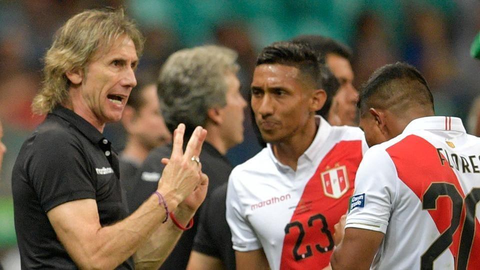 Peru's coach, Argentine Ricardo Gareca, gives instructions to Peru's Christofer Gonzales (C) and Edison Flores.