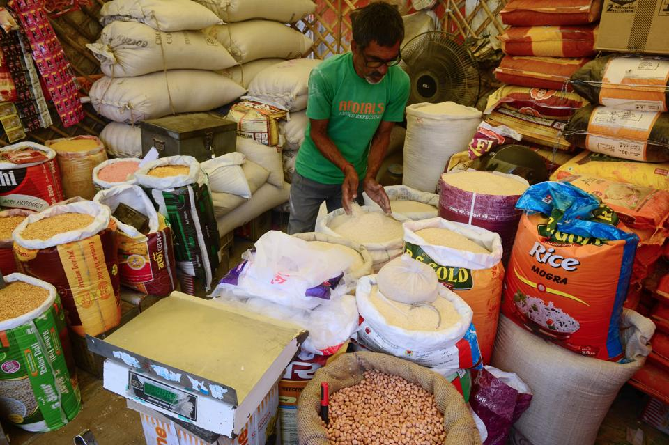 An Indian shopkeeper selling grains and legums waits for customers at a market in Allahabad on July 5, 2019.