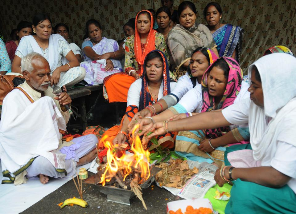 Contractual auxiliary nurse midwife (ANM) and general nurse midwife (GNM) doing rituals of