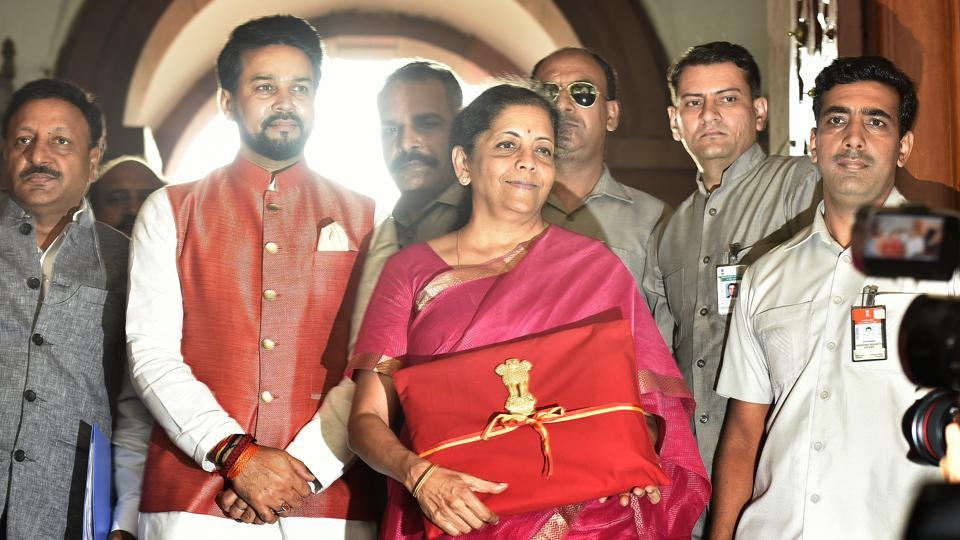 New Delhi, India - July 05, 2019: Minister of Finance Nirmala Sitharaman seen holding the Budget folder--Bahi Katha wrapped in red cloth with the National Emblem along with Minister of State in the Ministry of Finance Anurag Thakur upon their arrival to present the Union Budget 2019-20 in the Lok Sabha, at Parliament House, in New Delhi, India, on Friday, July 05, 2019. (Photo by Raj K Raj / Hindustan Times)