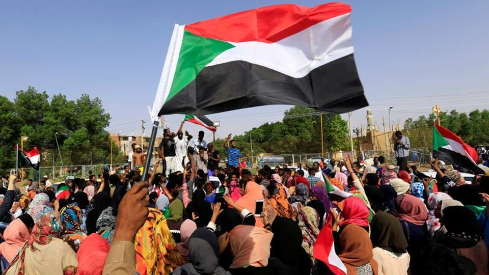Sudanese people chant slogans and wave their national flag as they celebrate, after Sudan's ruling military council and a coalition of opposition and protest groups reached an agreement to share power during a transition period leading to elections, along the streets of Khartoum, Sudan.