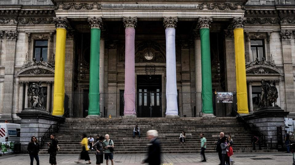 People pass by Brussels stock exchange building Beurs - Bourse with its columns wrapped with the colours of cycling jerseys, overall leader's yellow, best sprinter's green, best climber's polka dot and best young white one in Brussels centre. (Jeff Pachoud / AFP)