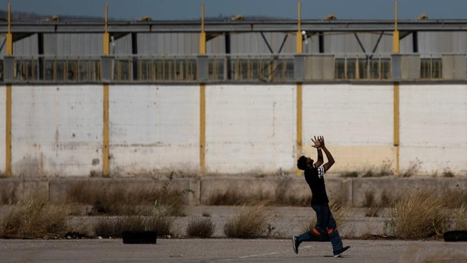 "A man tries to catch the ball during a tape-ball cricket game in a disused parking lot for trucks in an industrial area in Elefsina. ""I love cricket. I'm crazy for cricket. I'm 30 years old and I'm playing for 20 years,"" said Awais Mughal, a delivery worker who arrived in Greece a decade ago.  (Alkis Konstantinidis / REUTERS)"