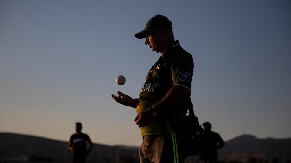 "Pakistani former Greece national cricket team player Mehdi Khan Choudhry throws a ball in the air as he umpires a game of tape-ball cricket in a disused parking lot for trucks. ""Many people play cricket here but we have no grounds in Athens,"" he said. (Alkis Konstantinidis / REUTERS)"