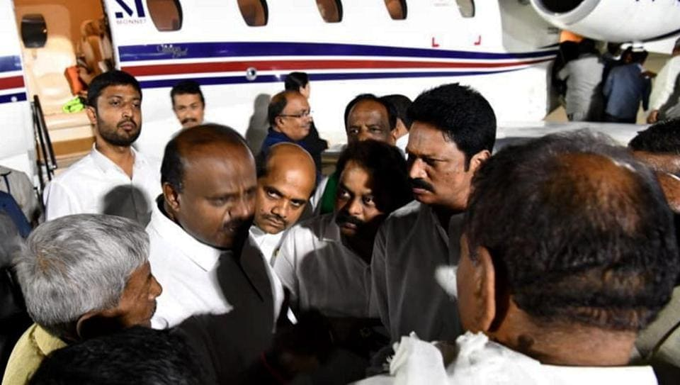 Karnataka Chief Minister H D Kumaraswamy talks with party MLA's and ministers at the HAL airport, Bengaluru, on his return from a 10-day personal trip to US amid political turmoil in the state.